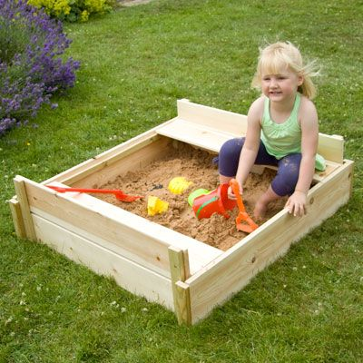 The wooden lid simply stores away to form two bench seats.  Sand and toys not included.